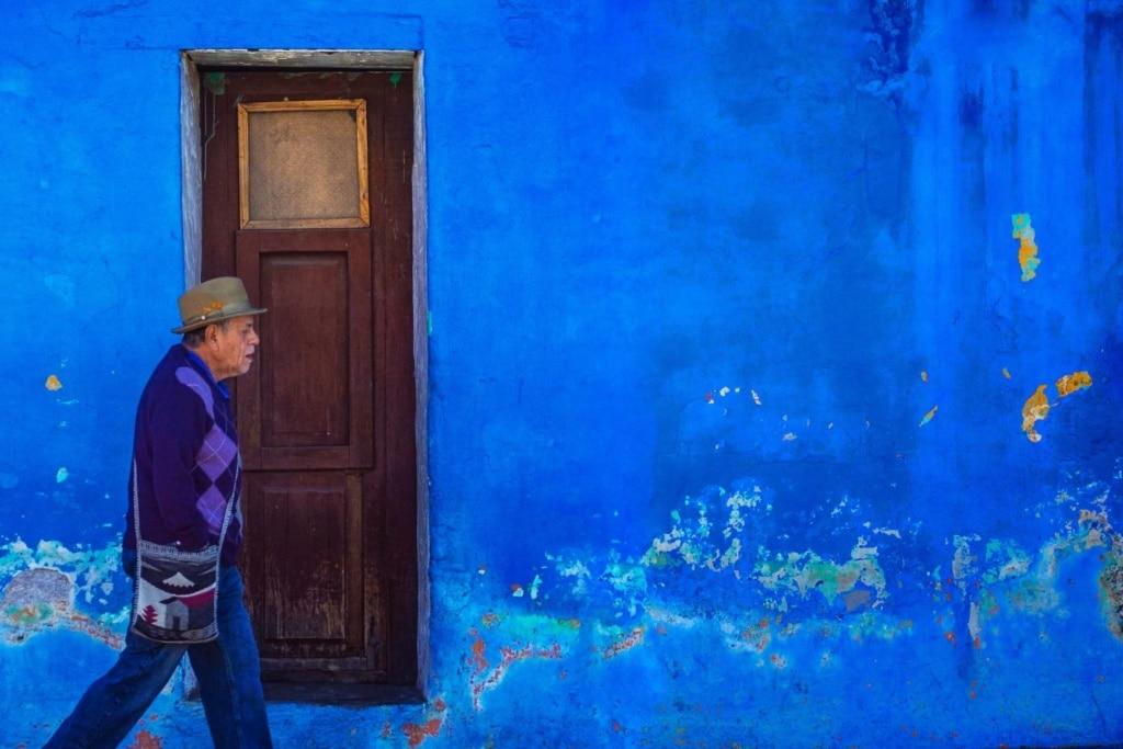 Älterer Mann geht in Antigua (Guatemala) an einer blauen Hauswand vorbei