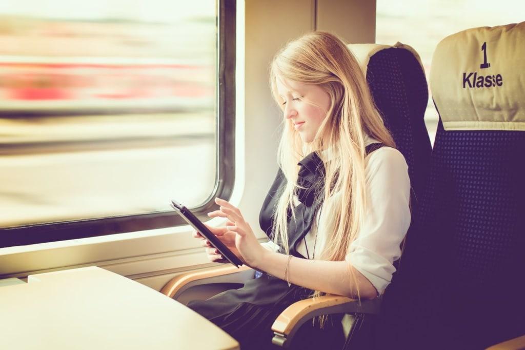 Frau mit blonden Haaren sitzt im Abteil der 1. Klasse