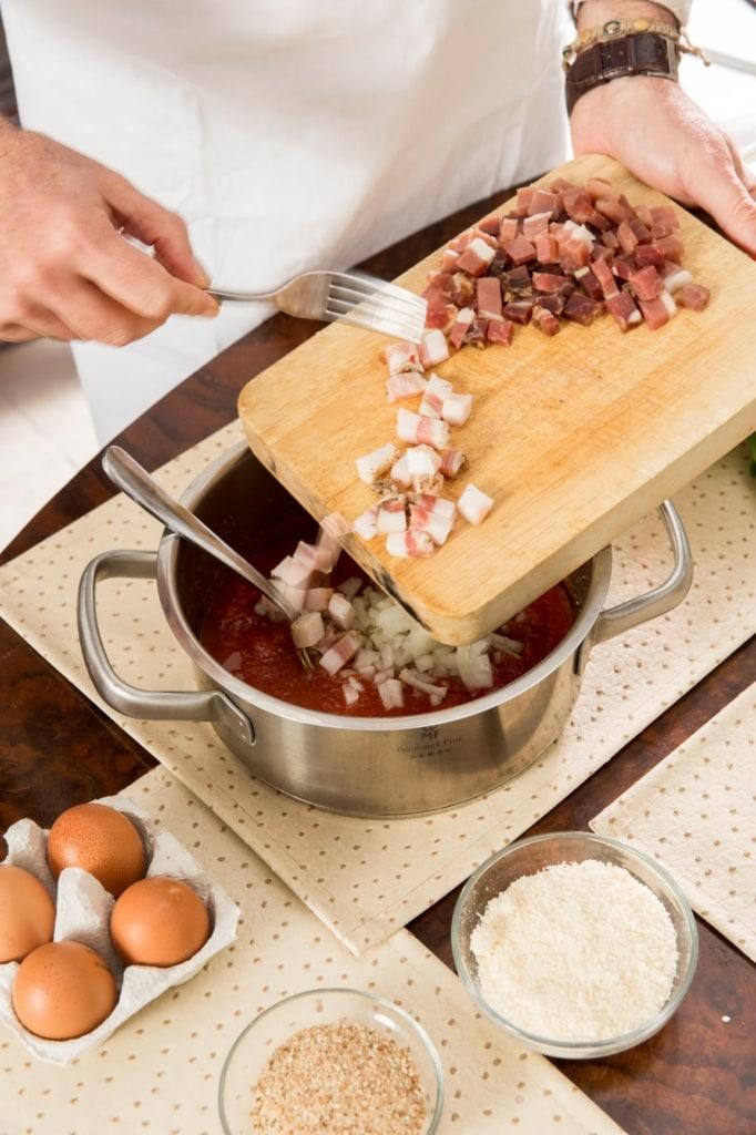 Koch hält Holzbrett mit Speck in der Hand