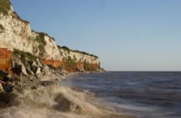 Der Norfolk Coast Path führt entlang rotbrauner Klippen, oft verläuft der Pfad direkt am Strand.