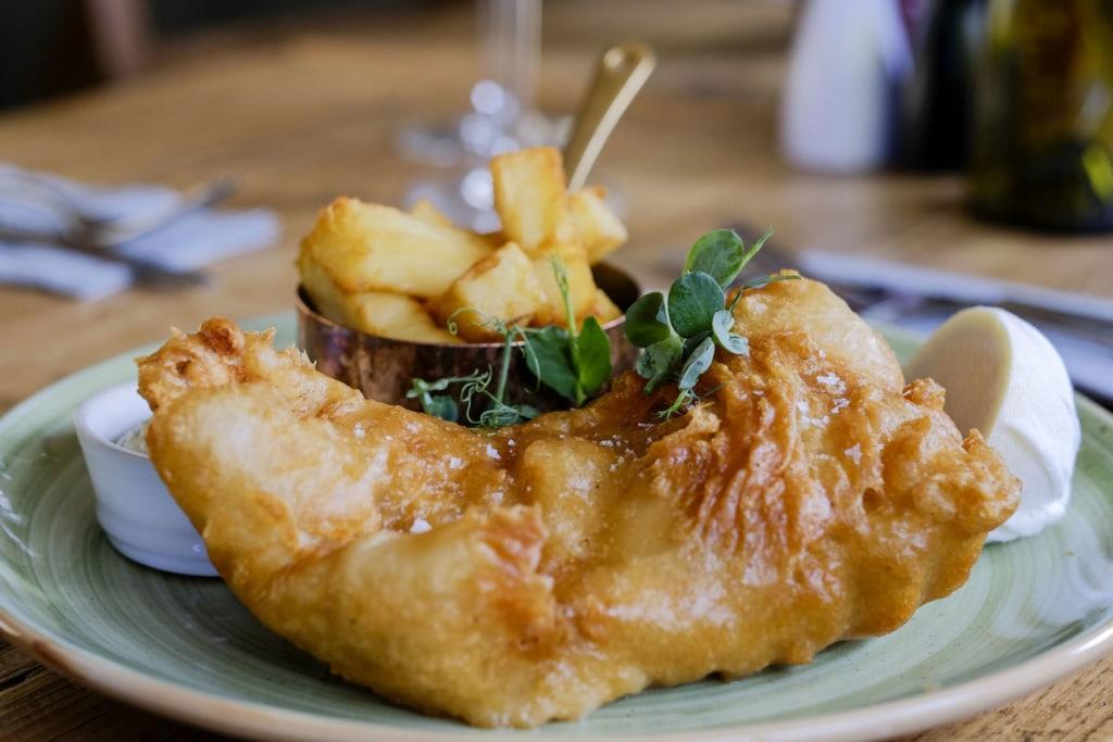 Eine Portion Fish'n'Chips angerichtet auf Teller in einem Pub in England