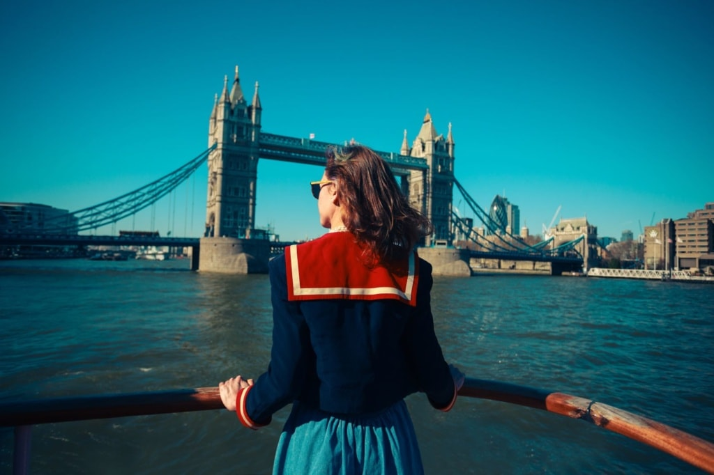 Frau an der Reeling eines Ausflugsbootes auf der Themse in London