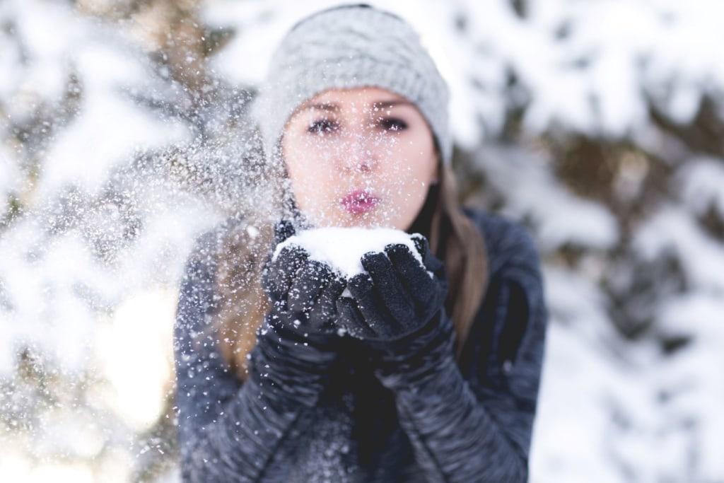 Frau in Winterlandschaft hält Schnee in der Hand, den sie wegpustet