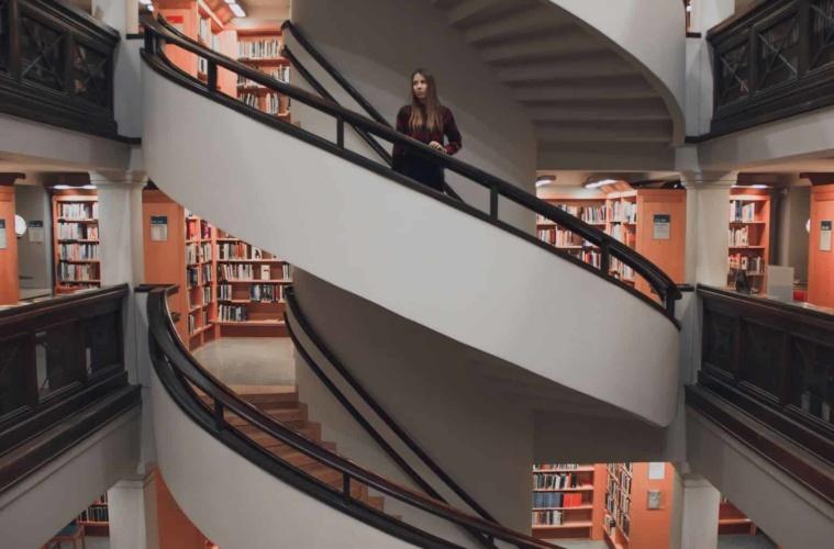 Frau steht auf Wendeltreppe