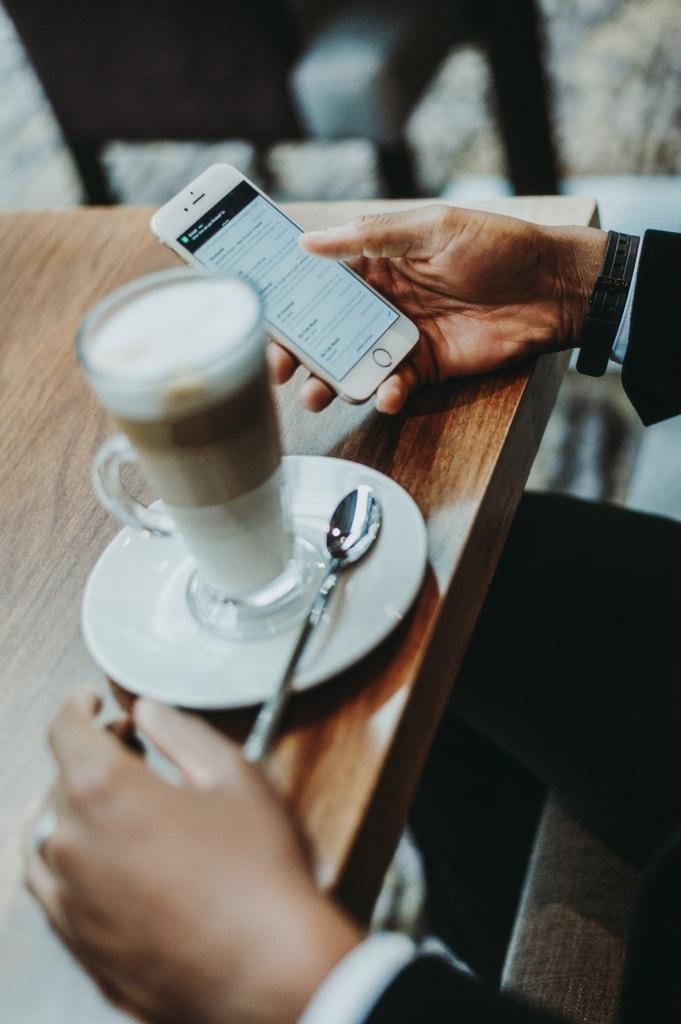 Person hält Handy in der Hand, auf Tisch ein Latte Macciato