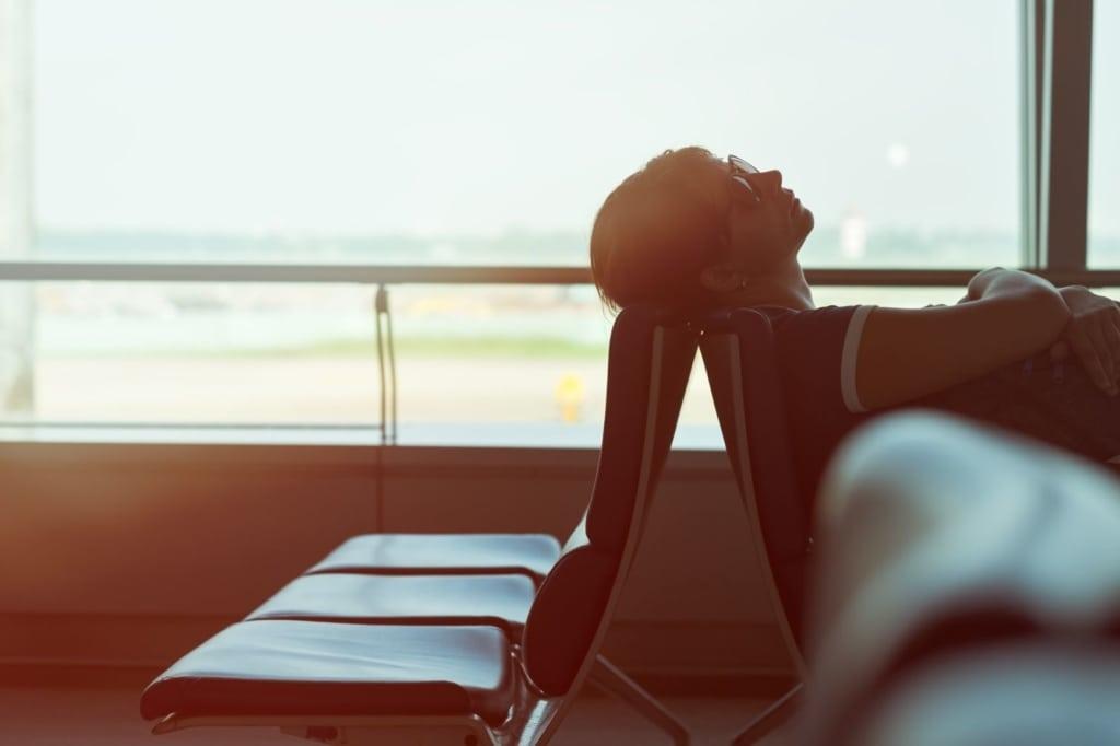frau schläft auf sitz im flughafen gebäude
