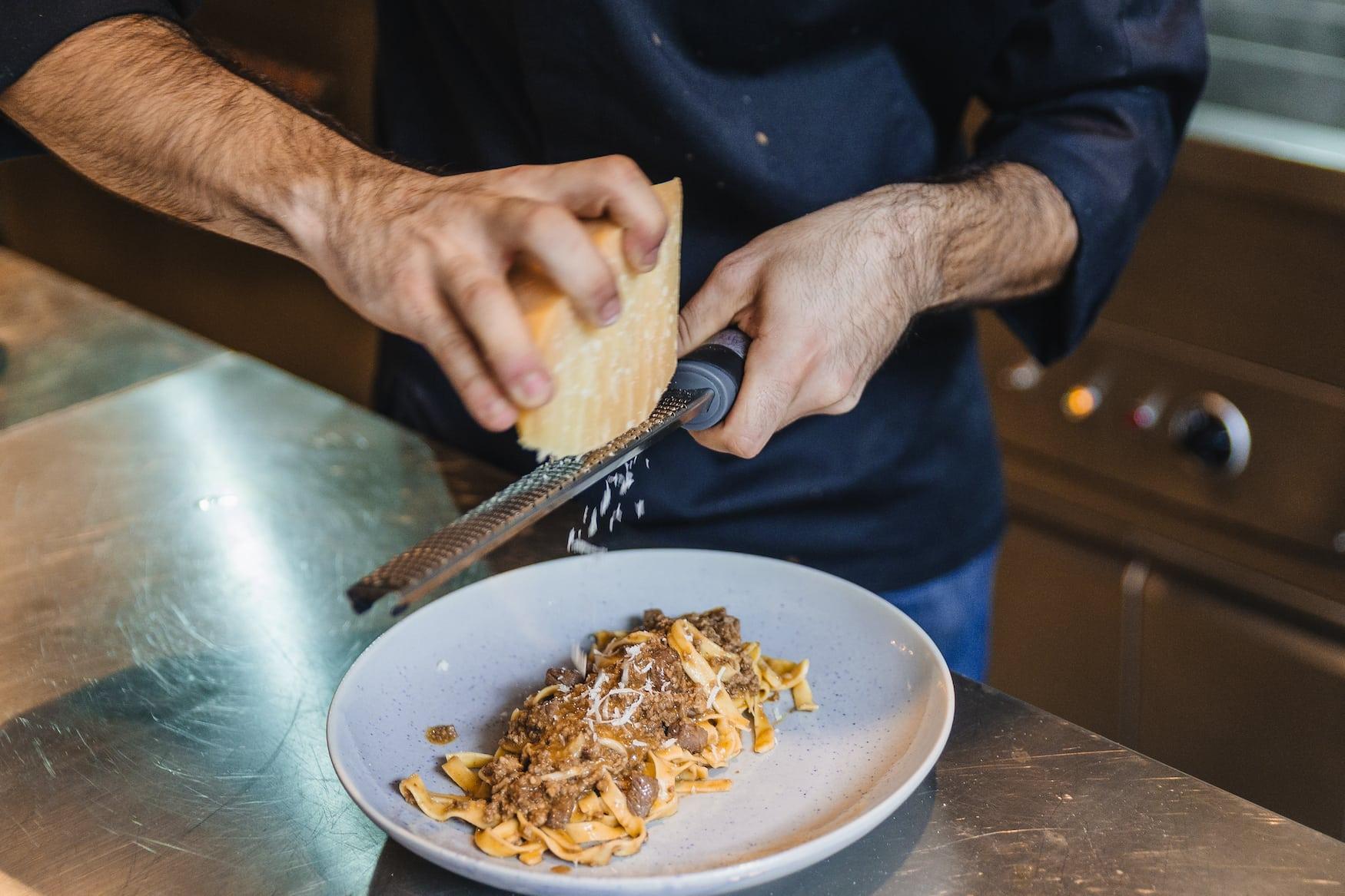 Koch reibt Käse über Tagliatelle al Ragu
