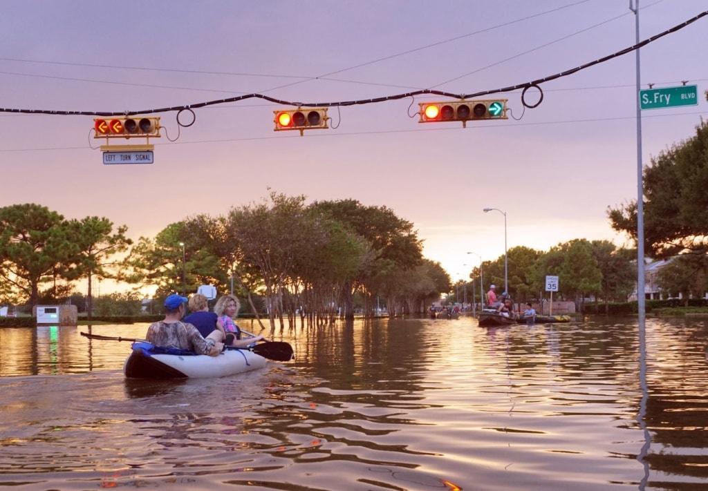 Menschen im Schlauchboot auf überfluteter Straße