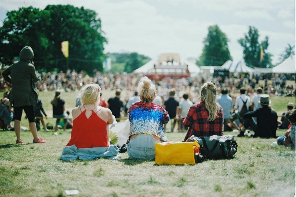 Festivalbesucherinnen auf Wiese sitzend