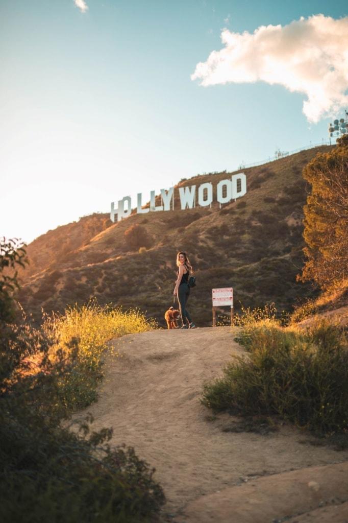 Frau mit Hund auf Weg, im Hintergrund Hollywood-Sign