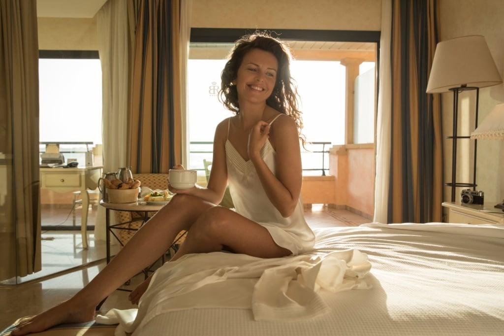 Frau im Hotelzimmer auf Bett mit Tasse