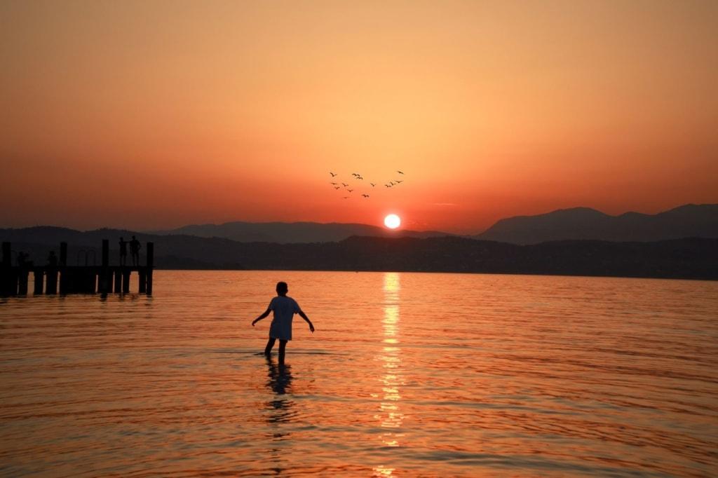 Junge bei Sonnenuntergang im Gardasee
