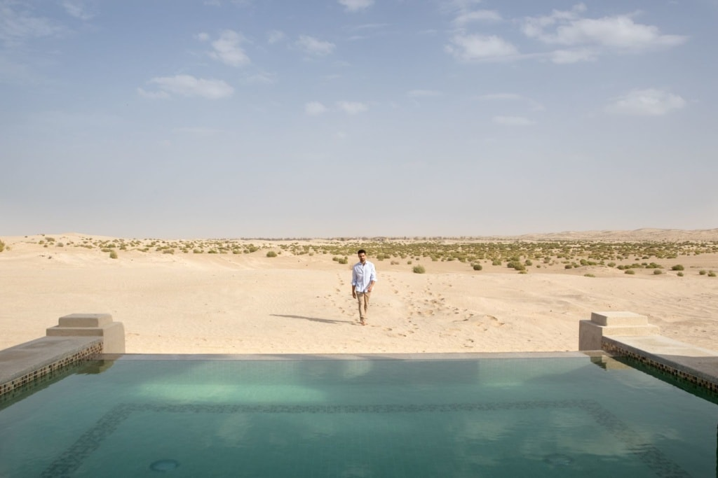 Mann hinter Pool im Jumeirah Al Wathba Desert Resort