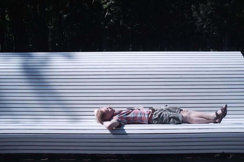 Mann liegt in Minsk auf großer Bank in Sonne