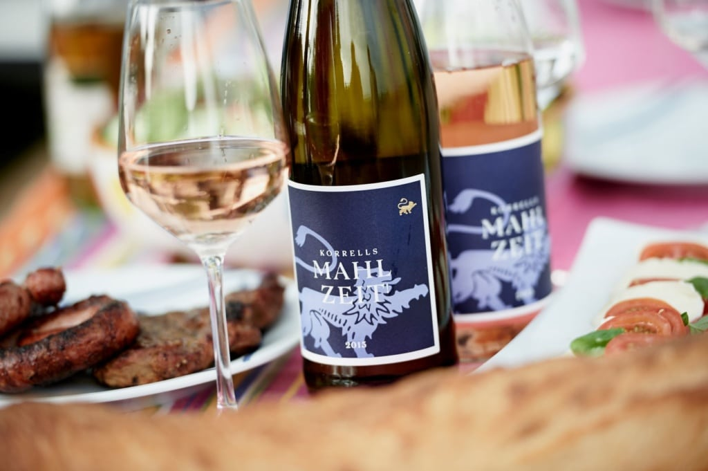 Weinflasche neben Salat und Gegrilltem