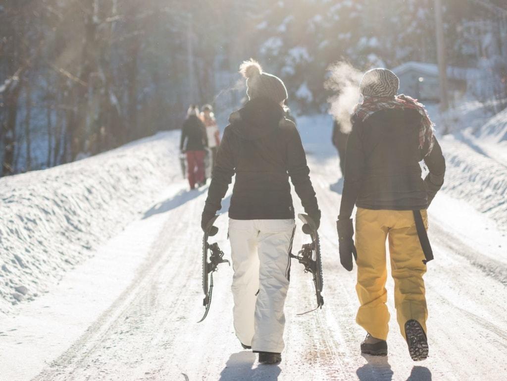Zwei Skifahrerinnen laufen einen Weg entlang