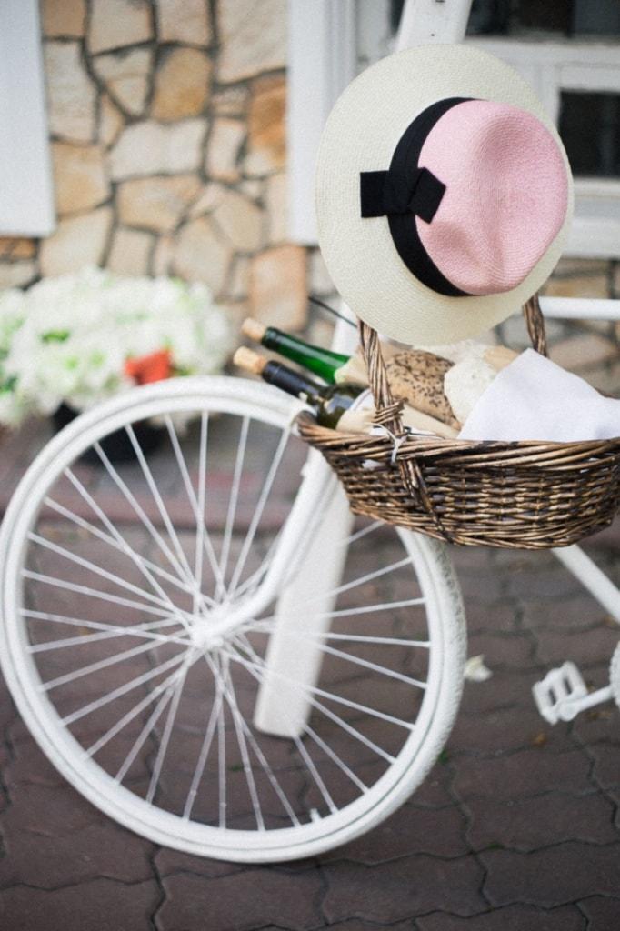 Weißes Fahrrad mit Sonnenhut und Korb mit Weinflaschen am Lenkrad