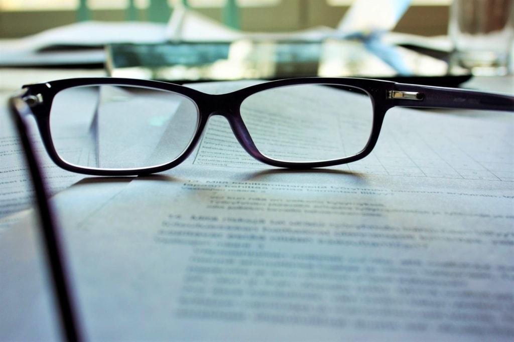 Brille auf bedruckten Blättern liegend