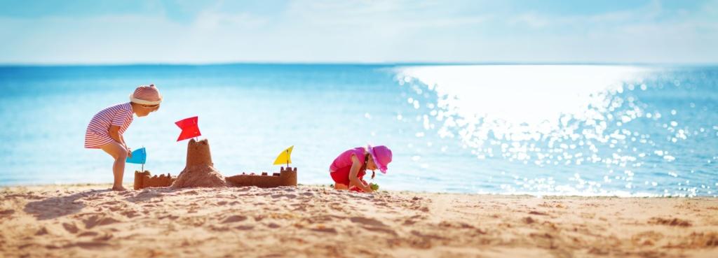 Zwei Kinder bauen Sandburg am Strand