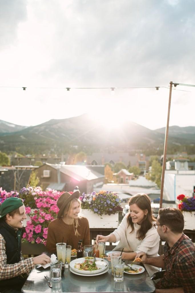 Zwei Männer und zwei Frau sitzen auf einer Terrasse beim Essen