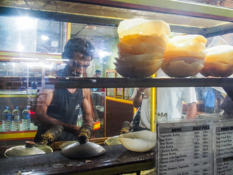 Srilankischer Mann brät Hoppers an einem Street Food Stand