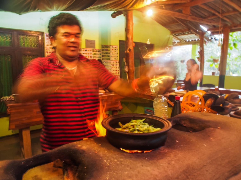 Kochkursleiter Lanka rührt die verschiedenen Currys um