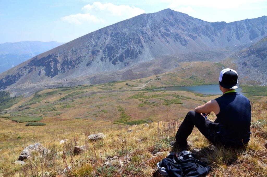 Wanderer blickt sitzend auf Panorama und See in Colorado