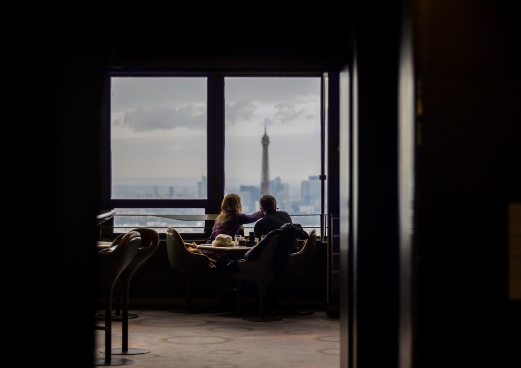 Mann und Frau sitzen auf Sesseln in einer Hochhaus-Bar