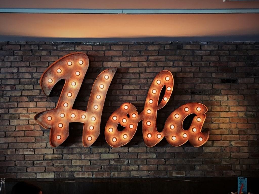 Hola-Schriftzug vor Backstein-Ziegelwand
