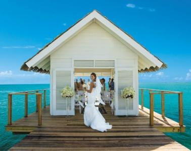 Braut vor Hochzeitsgäste auf Steg in der Karibik