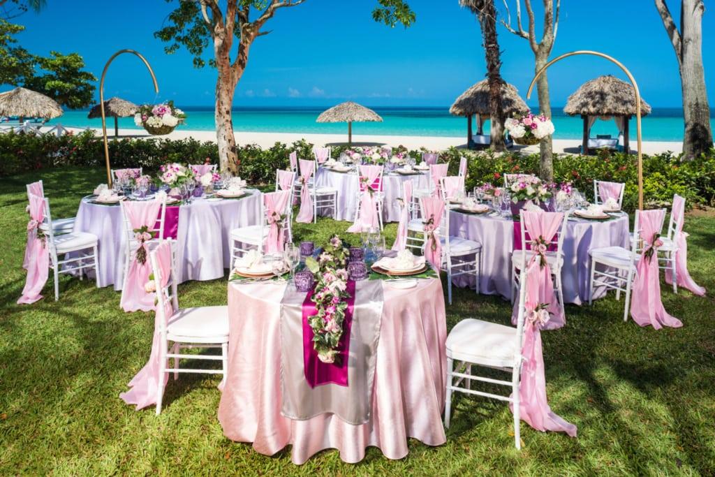 In Farbe pink gedeckte Tische bei Hochzeit am Strand