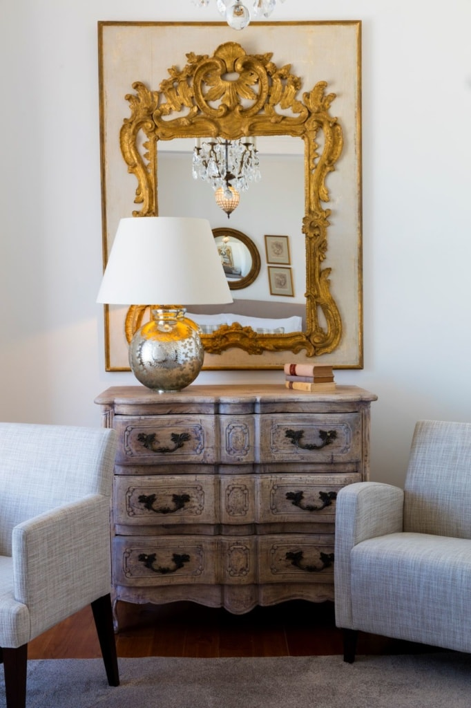 Kommode, Sessel und Spiegel in einem Zimmer im Grand House Algarve