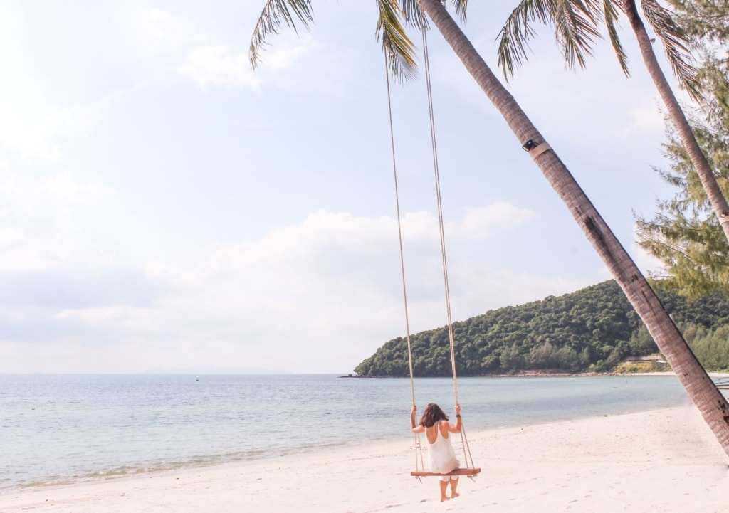 Frau auf Schaukel an Palme am Strand in Thailand