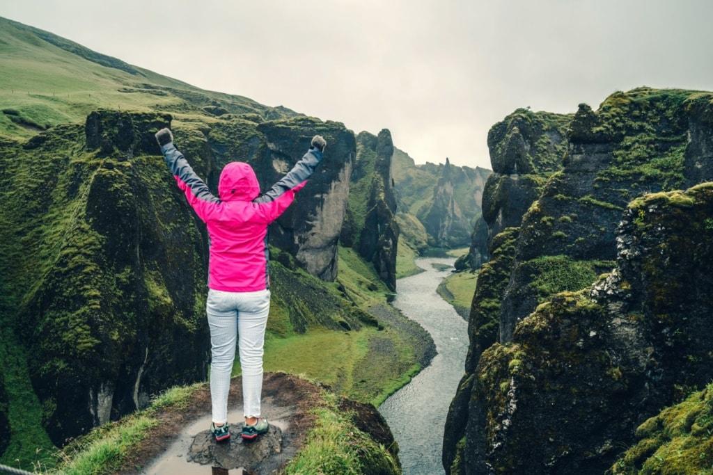Frau mit hochgestreckten Armen am Fjadrárgljúfur Canyon in Island