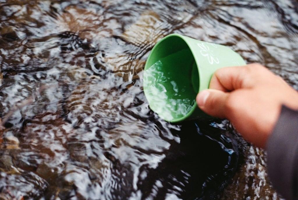 Grüne Tasse im Bach