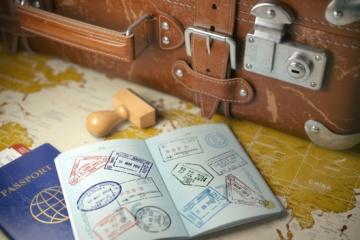 Reisepässe mit Stempel und Koffer