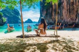 Frau im Bikini auf Schaukel am Strand in Thailand
