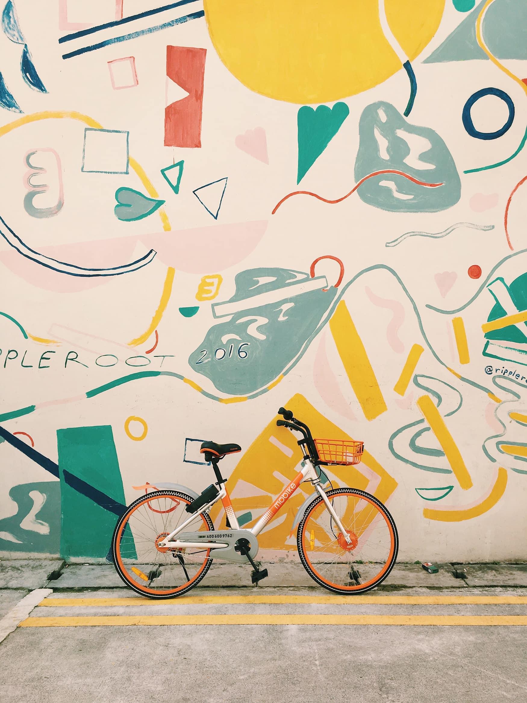Fahrrad lehnt an bunter Hauswand in Singapur