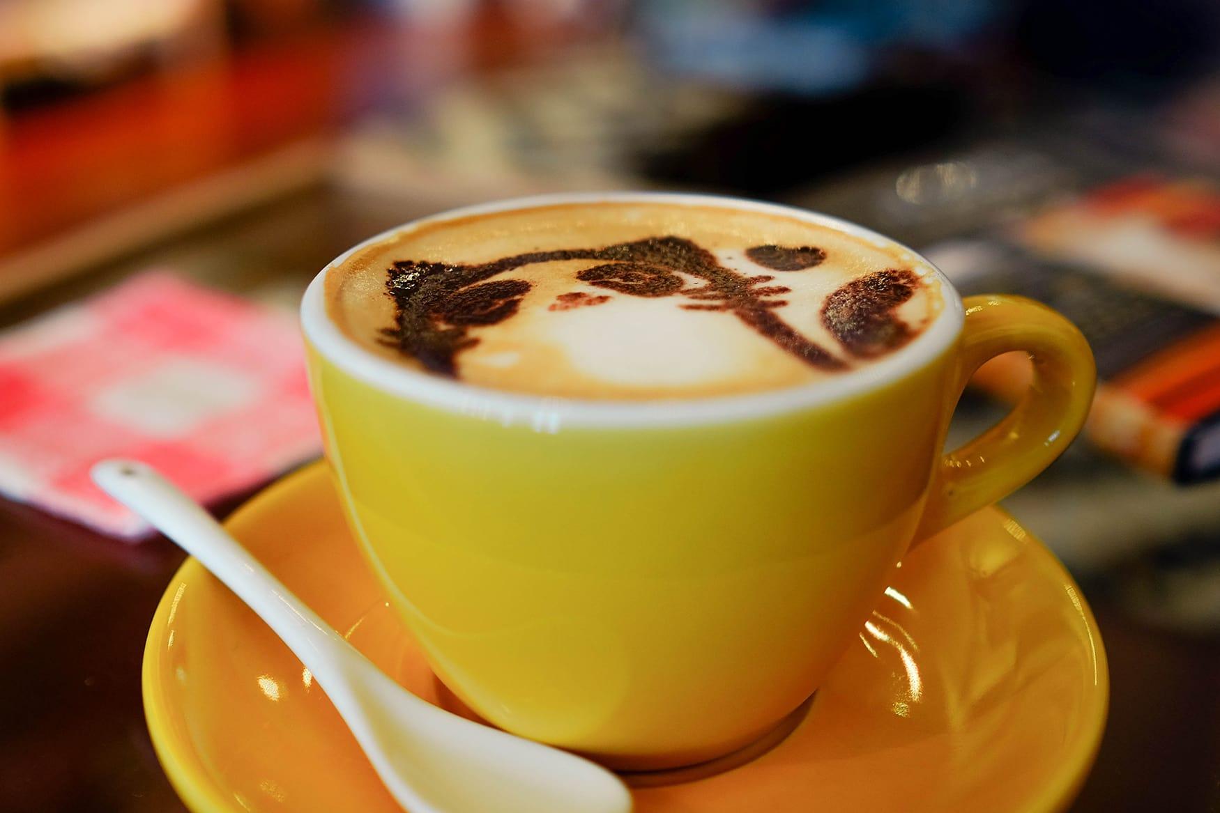 Gelbe Tasse Kaffee in Café