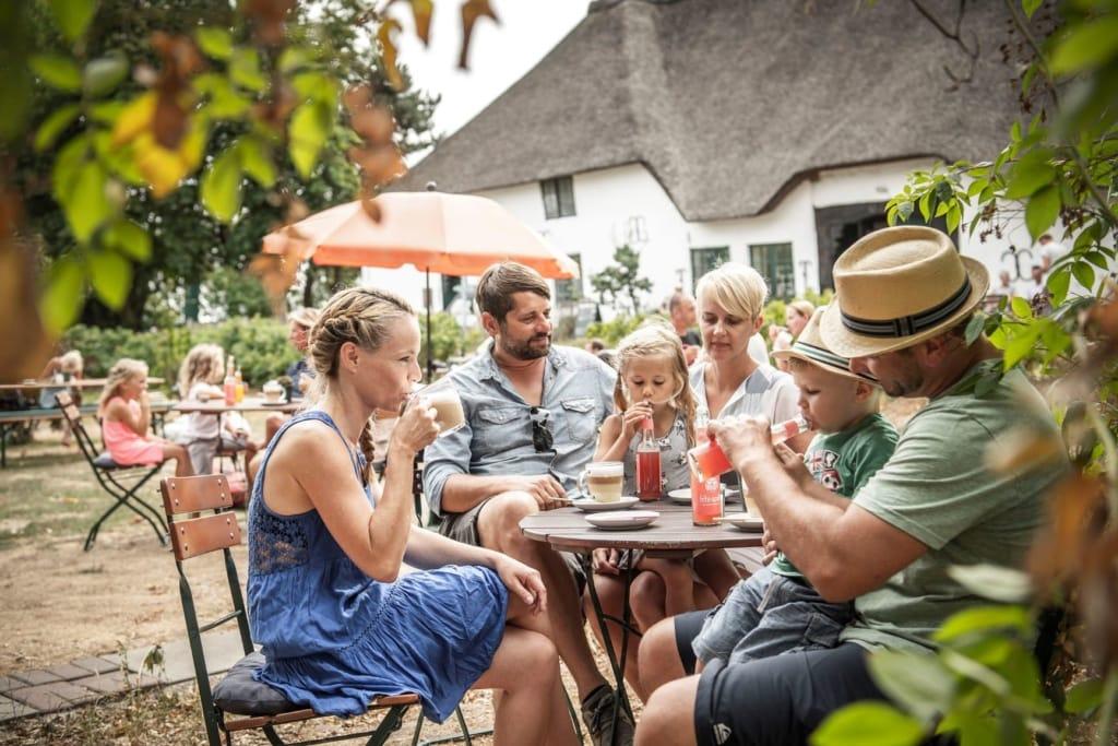 Familie an einem Tisch in einem Hofcafe in St. Peter-Ording