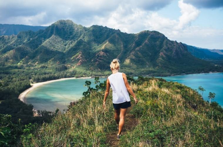 Blonde Wanderin blickt bei einer klassischen Hawaii-Wanderung über den Ozean.
