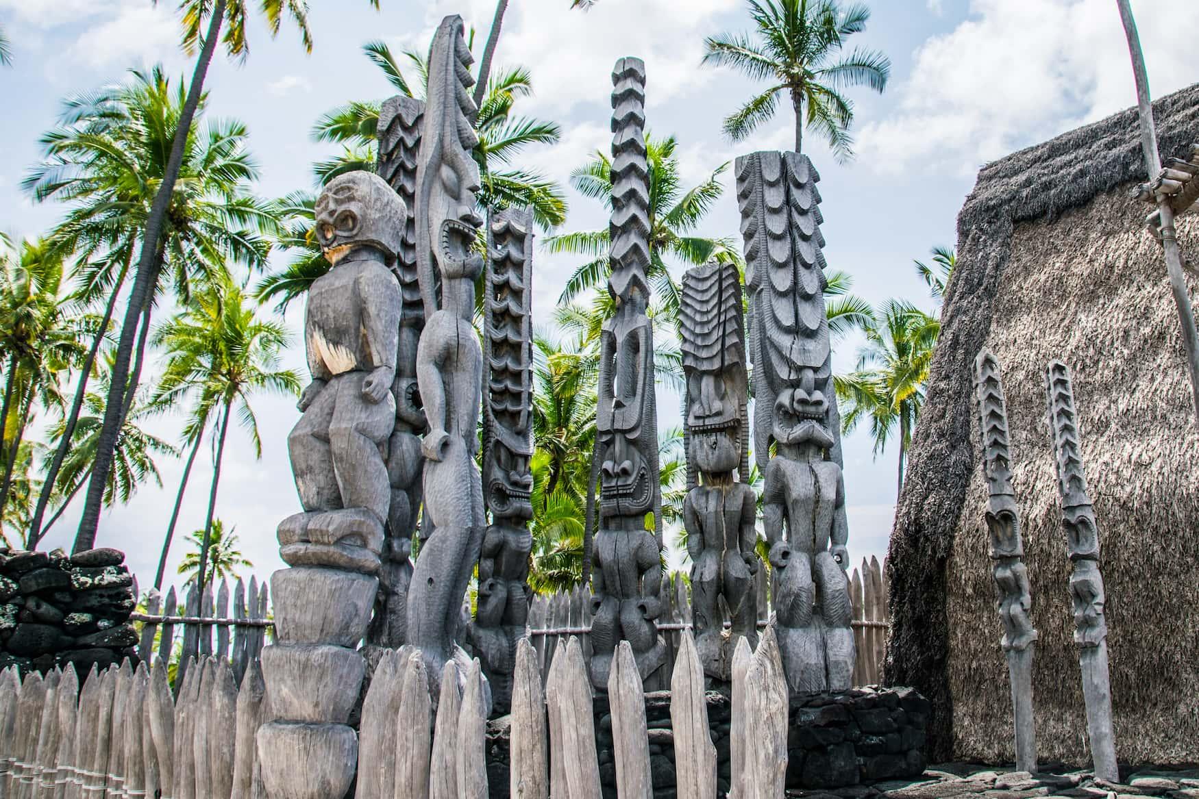 Uralte Tiki-Holzschnitzereien im polynesischen Stil grüßen die Besucher des Ki'i Pu'uhonua O Honaunau Nationalparks auf der Big Island von Hawaii.