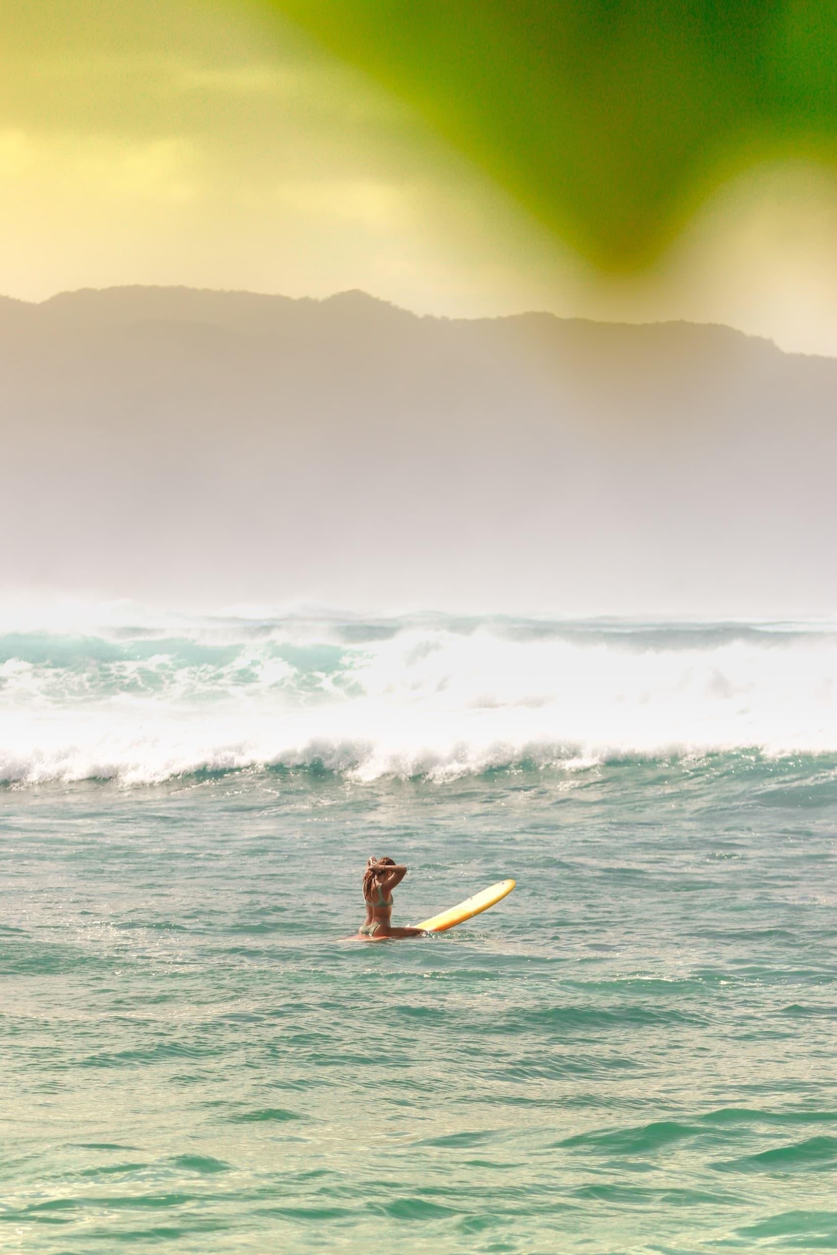 Surferin in den Wellen vor einer Insel von Hawaii