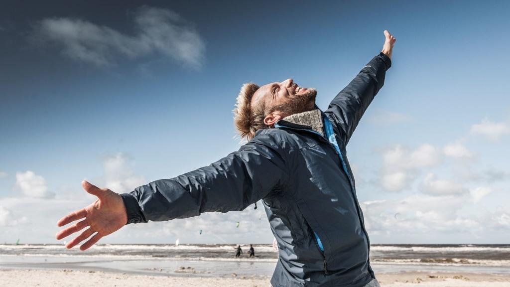 Mann breitet am Strand an der Nordsee die Arme aus