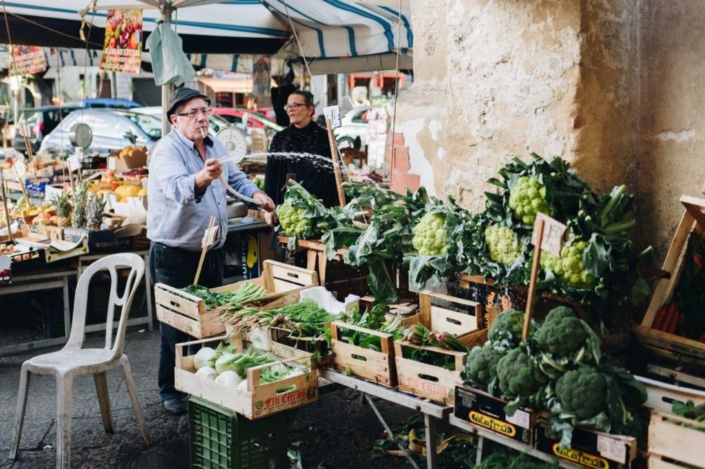 Älterer Mann besprüht Gemüse mit Wasser aus Schlauch