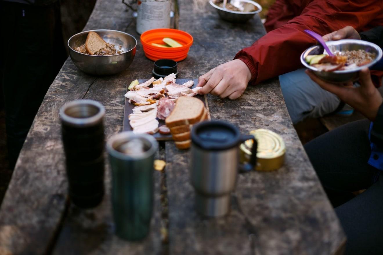 Holztisch bedeckt mit Brot und Wurst