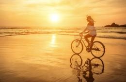 Frau fährt Fahrrad bei Sonnenuntergang am Strand