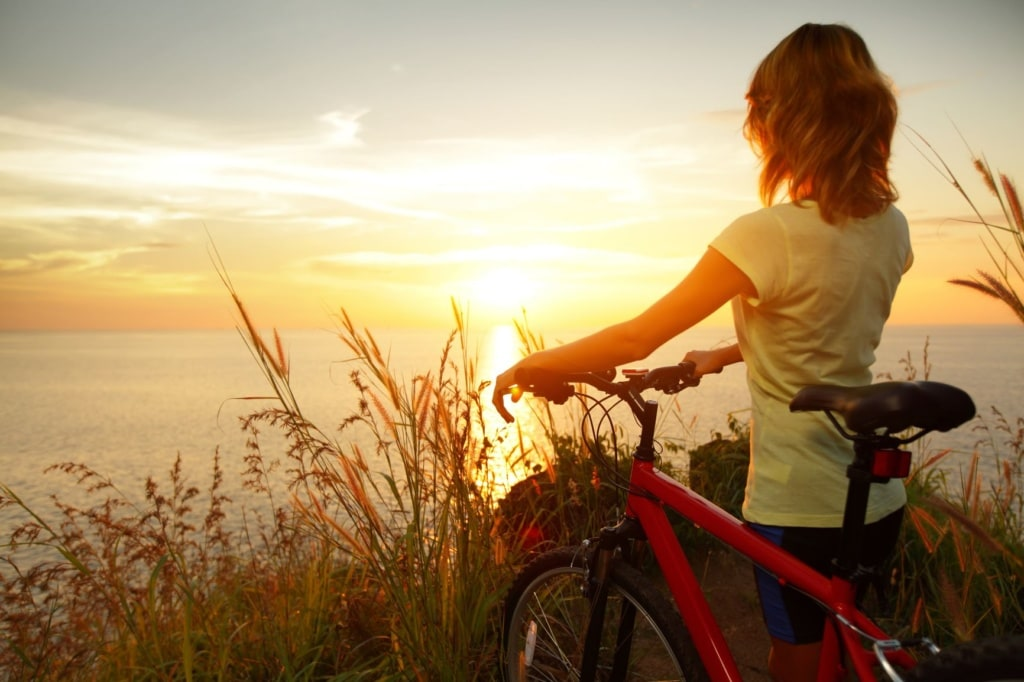 Frau mit Fahrrad blickt aufs Meer