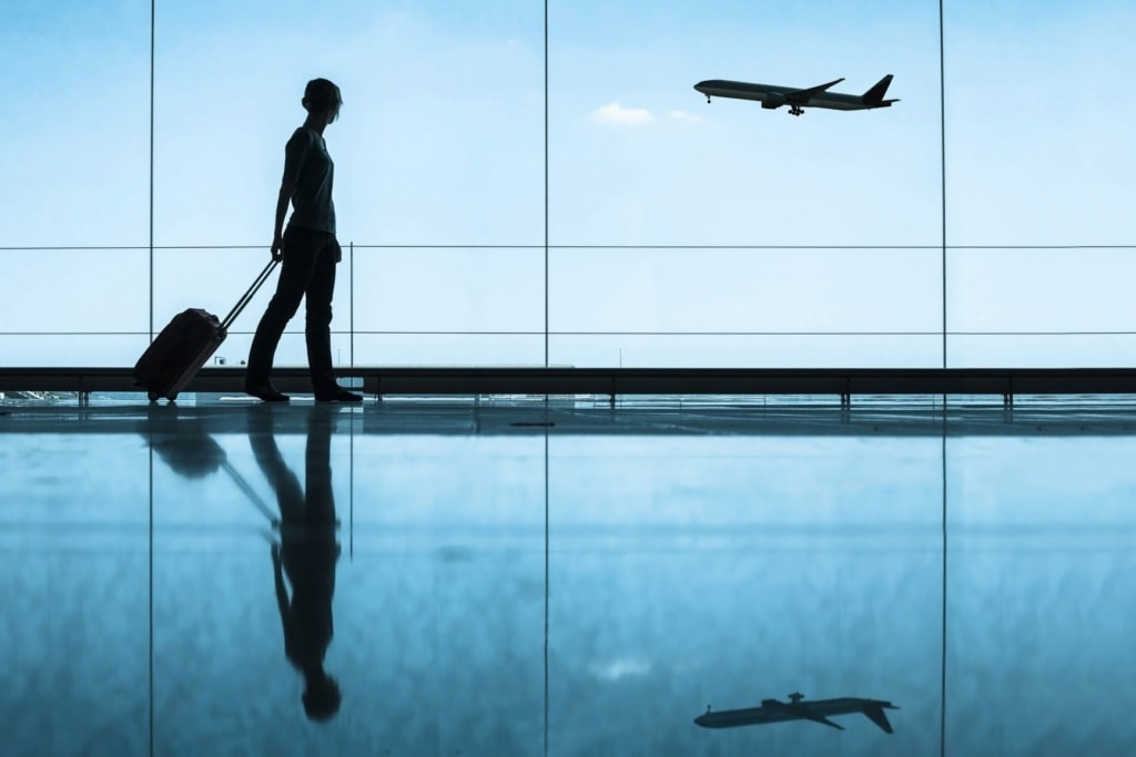Frau mit Rollkoffer im Flughafen