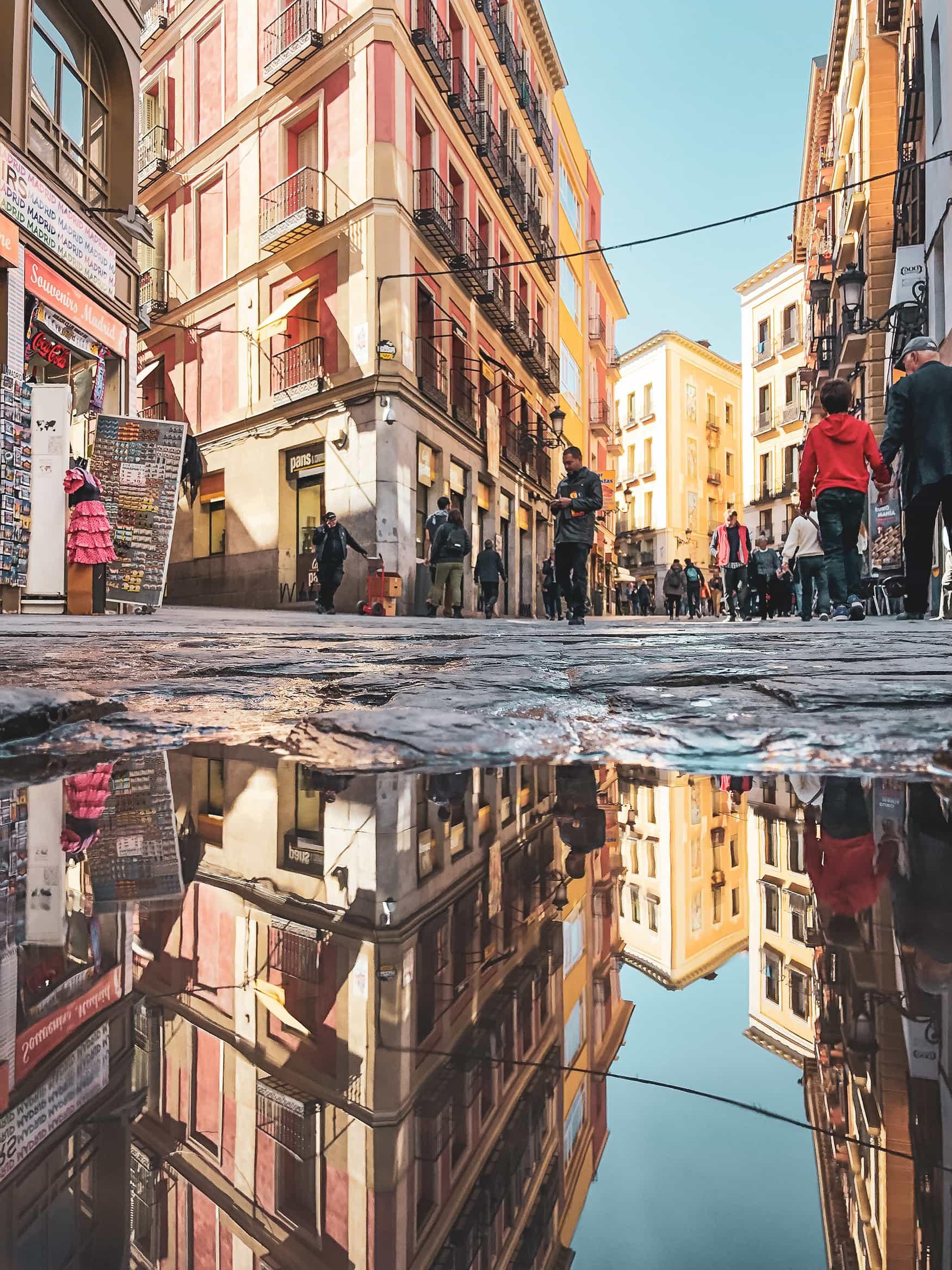 Häuserfassaden der Altstadt in Madrid spiegeln sich in Pfütze